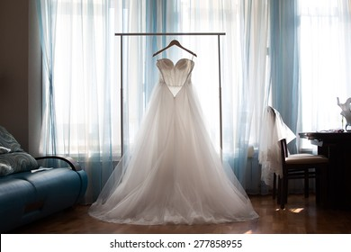 The perfect wedding dress with a full skirt on a hanger in the room of the bride with blue curtains
