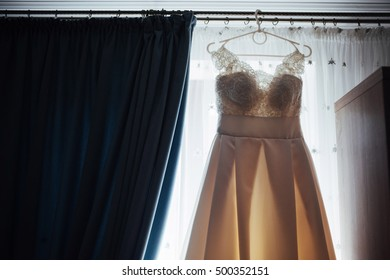 The perfect wedding dress with a full skirt on a hanger in the room of the bride