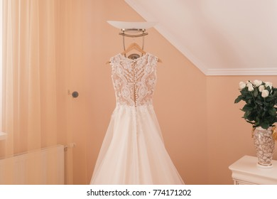 The perfect wedding white lace dress hanging on rack. Beautiful bridal dress on a hanger in the room of the bride over beige wall. Vase of white tender roses. Fashion look