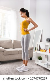 Perfect weight. Slim young woman standing on scales and weighing herself, while holding her hands on the waist