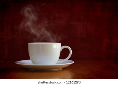 The perfect white cup with steaming coffee sitting on oak table on grungy burgundy background