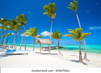 Perfect white sand beach with palm trees. Colorful exotic seascape with boats and pier near Zanzibar in Africa
