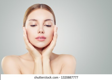 Perfect woman face. Beautiful girl touching her face her hands. Facial treatment, face lifting, anti aging and skin care concept.