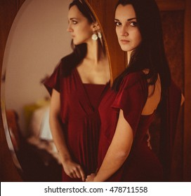Perfect woman looks over her shoulder while posing before a mirror
