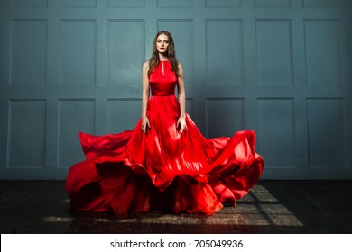 Perfect Woman in Red Dress. Beautiful Fashion Model on Blue Background
