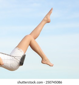 Perfect woman waxing hair removal legs swinging with the blue sky in the background