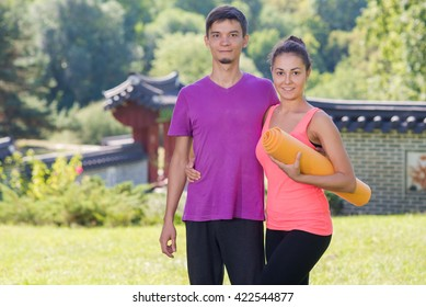 Perfect yoga workout. Beautiful couple is preparing for doing yoga. Pair yoga concept. Yoga outdoor class workout Acro-yoga.