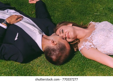 The perfect young couple Lies on the ground and kiss. Dark-haired Bride with jewelery in her head and a white lace dress on the grass.