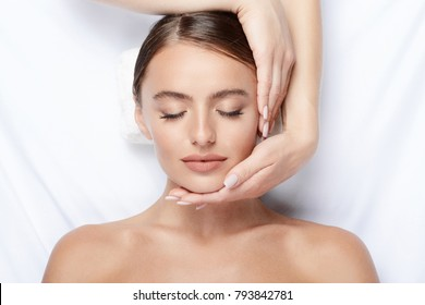 Perfect young girl with thick eyebrows and perfect skin doing facial massage, beauty photo concept, hands on face, skin care, relaxing in spa.