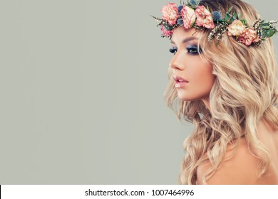 Perfect Young Model with Flowers on Head and Curly Hair Styling. Summer Woman, Blossom Beauty