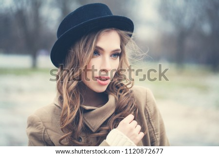 6f61bad3f59 Perfect young woman in black hat outdoors in park. Perfect female face  closeup