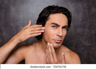 Perfection is a hard work even for men. Pampering, aging, acne, pimple, wrinkles, clear and clean, oily, dry skin concept. Cose up cropped photo of worried guy touching his cheek and look focused