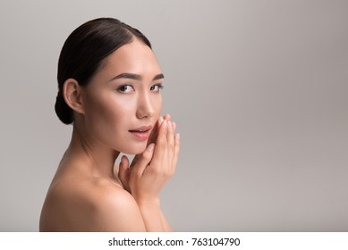 Perfection. Side view of elegant young naked asian girl with healthy complexion. She is looking at camera thoughtfully while touching her face tenderly. Isolated and copy space in right side