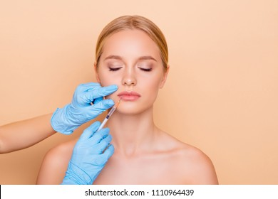 Perfection wellness wellbeing concept. Portrait of cute charming model with close eyes getting cosmetic injection in lips, shape correction, isolated on beige background