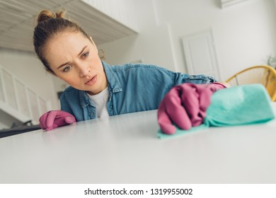 Perfectionism in clean and tidy. Close up portrait of serious young lady carefully washing dirty stains on table surface by patch at home