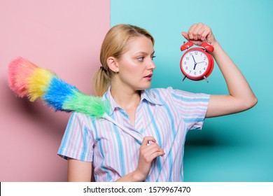 Perfectionism concept. Woman hold dust brush alarm clock. Everything must be perfect. Girl perfectionist. Perfectionist complex. Obsessive compulsive disorder. Cleaning time. Obsessed perfectionist.