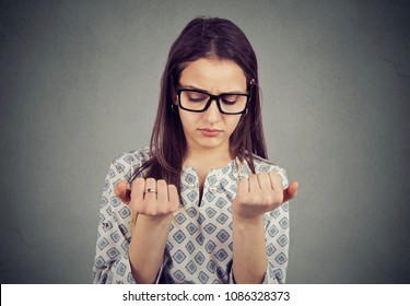 Perfectionist young woman looking at fingers nails obsessing about cleanliness