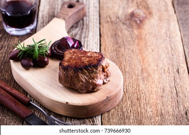 Perfectly cooked filet mignon served on wooden cutting board with roasted red onion and rosemary