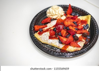 A perfectly folded crepe topped with glazed strawberries and blueberries and whipped creme and generously dusted and garnished with powdered sugar.