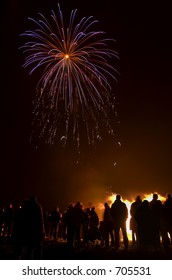Perfectly framed blue firework starburst with audience silhouetted against bonfire.