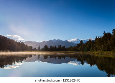 Perfectly reflection of Mount Cook on the Lake Matheson in Fox Glacier, West Coast, New Zealand in the morning blue sky
