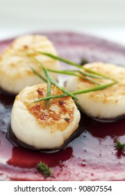 Perfectly seared scallop starter with bright cranberry and balsamic vinegar reduction