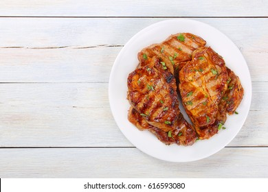 Perfectly seasoned, juicy, delicious grilled pork chops with strips  sprinkled with fresh coriander served on white plate,  on white wooden boards, view from above