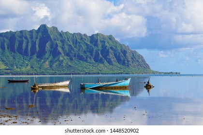 A Perfectly Still Kaneohe Bay Creates a Perfect Reflection of the Mountains and Old Boats in the Water.
