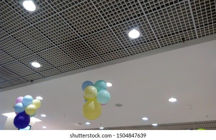 Perforated Grid ceiling and White Painted gypsum ceiling joints for an Retail shop during festival sale and decorated by hanging balloons