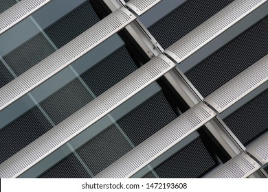 Perforated louvers over glass panels. Material background of steel or aluminium hi-tech architecture. Close-up fragment of modern industrial building. Diagonal geometric composition of parallel lines.