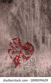 The perforated red leaf because eaten by pests and heart shaped on banana leaf background.