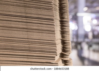 Perforated sheets of corrugated cardboard by stack on pallets - after assembly it will be cardboard boxes. Packaging of finished products in industrial production.