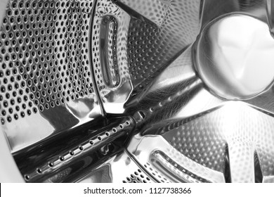 Perforated steel drum of washing machine. Inside view. Abstract industrial background