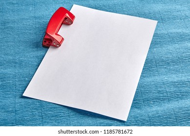 Perforating a blank sheet of white paper with a red steel hole puncher, blue background, close-up.