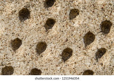 perforations in the concrete wall of the old temple. unusual surface texture with holes. Close-up. Work of the perforator.