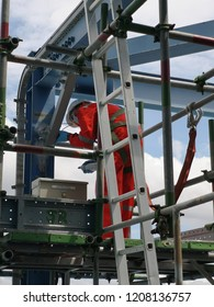 NDT inspector is perform magnetic testing on beam structure with full body safety harness