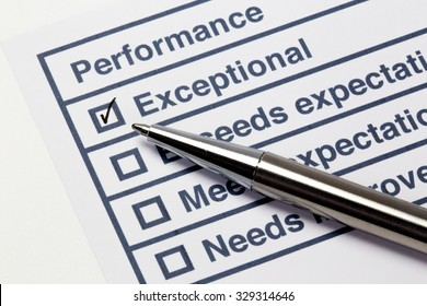 Performance evaluation paper with pen, check boxes and tick marks