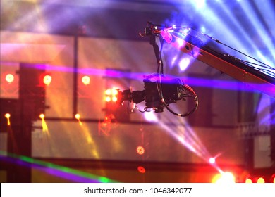 Performance moving lighting on construction light beam ray downward in yellow blue color, on Concert and Fashion Show stage ramp, camera vdo production on movement crane for broadcasting live Video