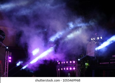 Performance moving lighting on construction light beam ray downward in yellow blue color, on Concert and Fashion Show stage ramp with smoke
