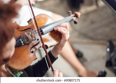 performance, music, orchestra concept. the most elegant musical instrument, violin, in tender hands of musician. it has four strings and gorgeous form of young woman