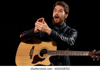 performance, searchlight, musician with a guitar claps his hands on a black background