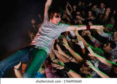 Performer body surfing across audience at concert