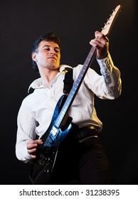 performer playing the guitar against dark background
