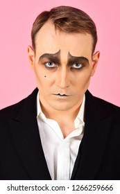 Performing drama. Theatre actor miming. Mime artist. Mime with face paint. Man with mime makeup. Stage actor miming. Theatrical performance art and pantomime. Comedian or tragedian performer.