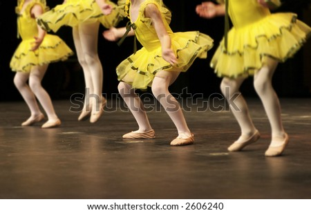 Performing on stage, a group of young dancers show off their talent and bright costumes - image highlights a narrow depth of field