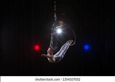 Performs a circus girl actress. Circus aerial gymnast on the hoop. Acrobatics. Teenager performs an acrobatic trick in the air