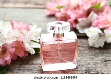Perfume bottle with alstroemeria flowers on grey wooden table