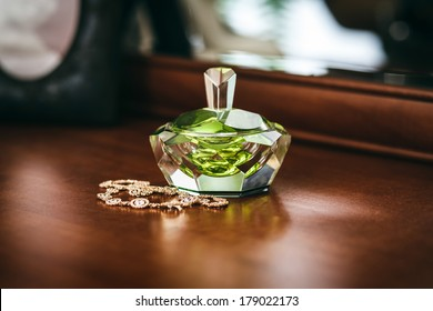 Perfume bottle with a beautiful green ruby shine and jewelry on table. Pleasant blur the background