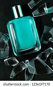 perfume bottle with broken glass on black
