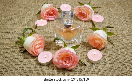 perfume in bottle, burning candles and pink roses, gift concept